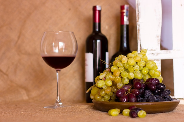 Błękitni i zieleni winogrona na glinianym brown naczyniu. butelka z czerwonym i
