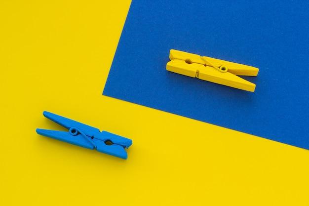 Błękitni i żółci clothespins na tle