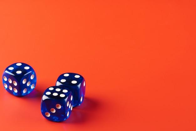 Błękitni kostka do gry na czerwień stole z copyspace