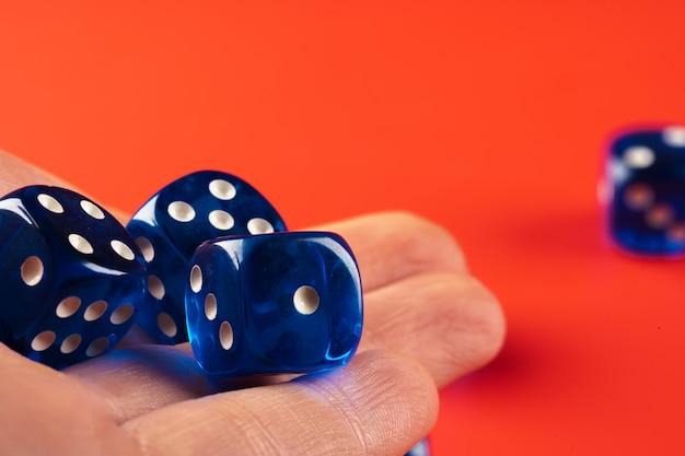 Błękitni kostka do gry na czerwieni powierzchni zakończeniu up