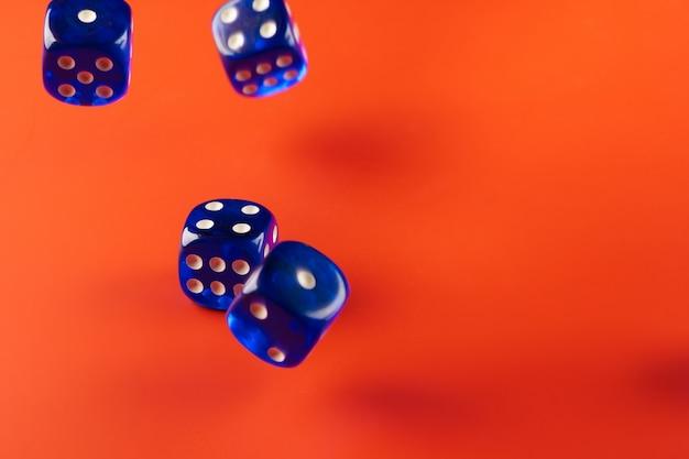 Błękitni kostka do gry na czerwonym tła zakończeniu up