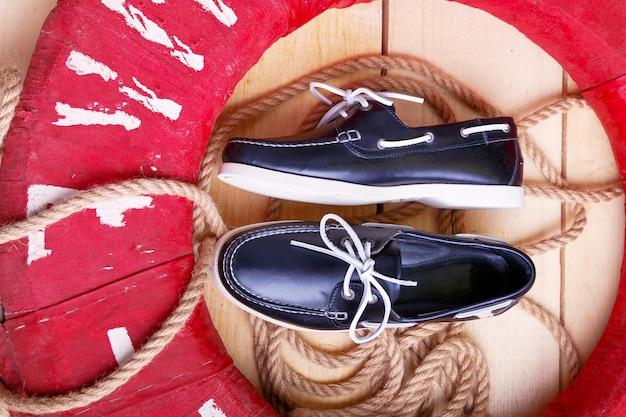 Błękitni łódź buty na drewnianym tle blisko czerwonego lifebuoy i arkany.
