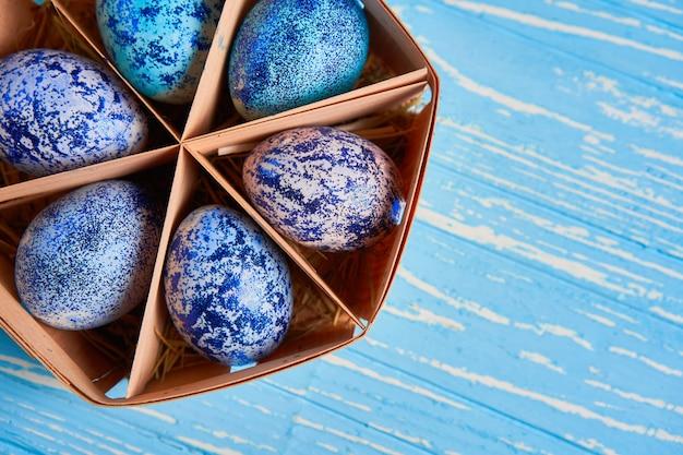 Błękitni wielkanocni jajka w koszu na drewnianym tle