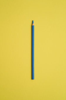 Błękitny barwiony ołówek odizolowywający na koloru żółtego stole