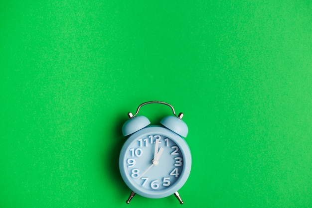 Błękitny budzik przeciw zielonemu tłu