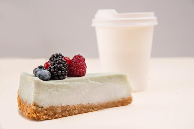 Błękitny cheesecake blisko papierowej filiżanki odizolowywającej