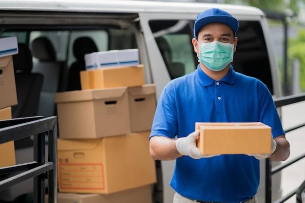 Błękitny doręczeniowy azjatykci mężczyzna trzyma drobnicowego karton