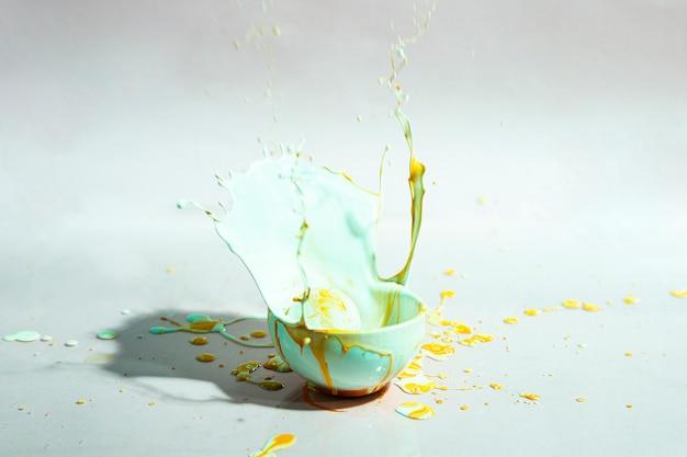 Błękitny i żółty farby pluśnięcie i filiżanka abstrakta tło