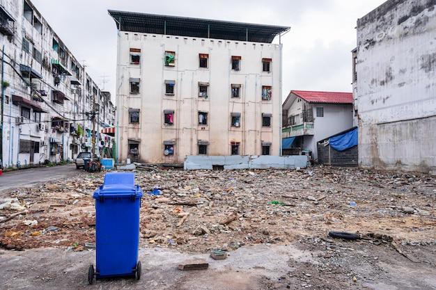 Błękitny kosz na śmieci z starym budynkiem