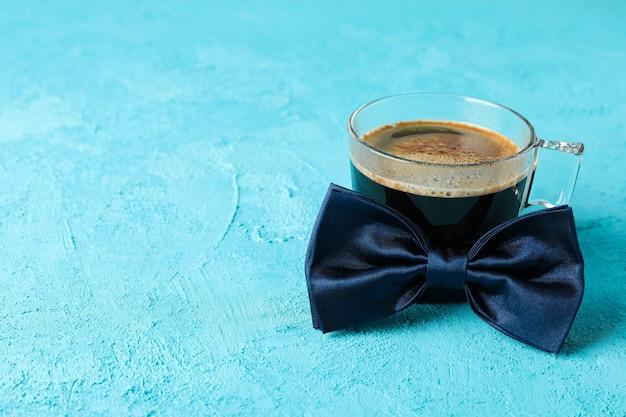 Błękitny łęku krawat i filiżanka kawy na koloru tle, przestrzeń dla teksta
