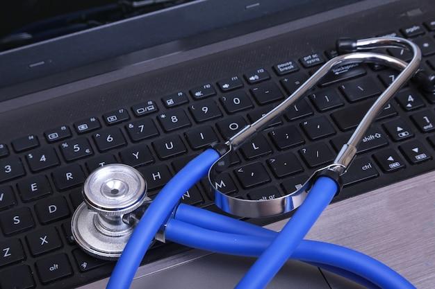 Błękitny medyczny stetoskop na ciemnym laptopie