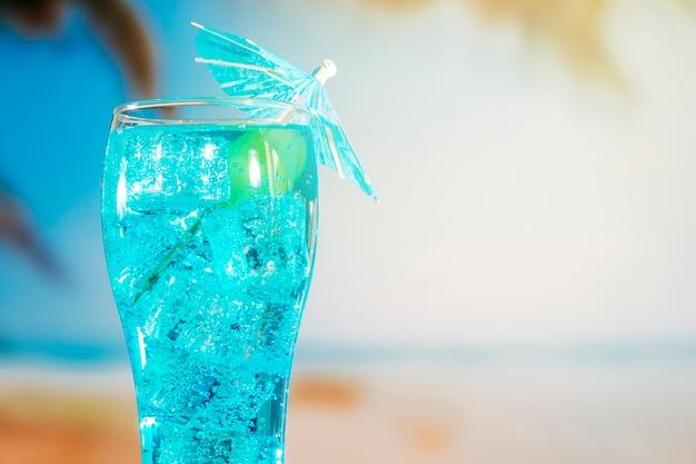 Błękitny napój z kostkami lodu w parasol dekorującym szkle