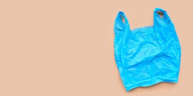 Błękitny plastikowy worek na browm tle.