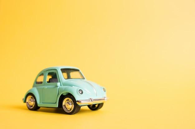 Błękitny retro zabawkarski samochód na kolorze żółtym. koncepcja podróży latem. taxi