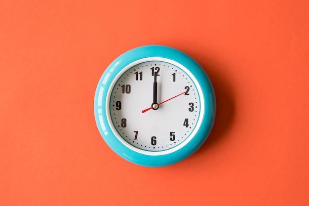 Błękitny ścienny zegar na pomarańczowym tle