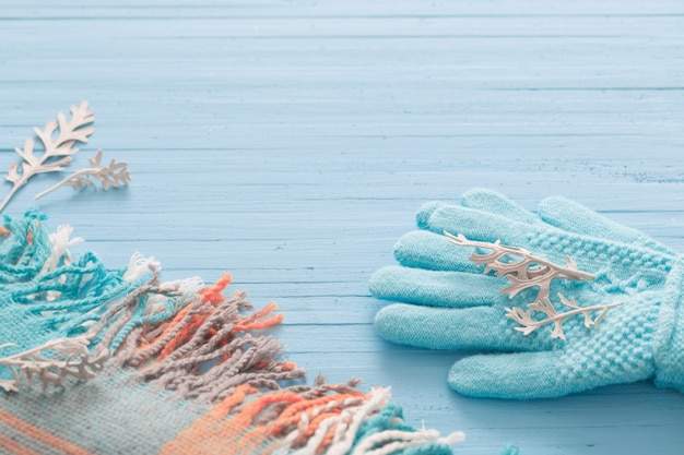 Błękitny szalik na drewnianym tle i rękawiczki