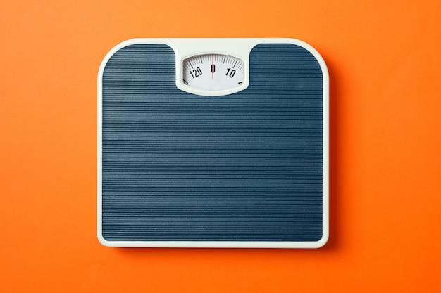 Błękitny ważenie waży na pomarańczowym tle, odgórny widok
