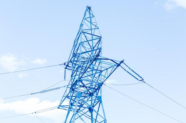 Błękitny wysoki woltażu wierza na niebieskiego nieba tle. linie energetyczne w mieście.
