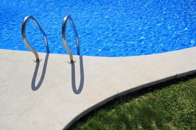 Błękitnych płytek pływacki basen z zielonej trawy ogródem
