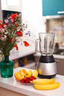 Blender i owoce leżące na stole w kuchni. koncepcja zdrowego odżywiania
