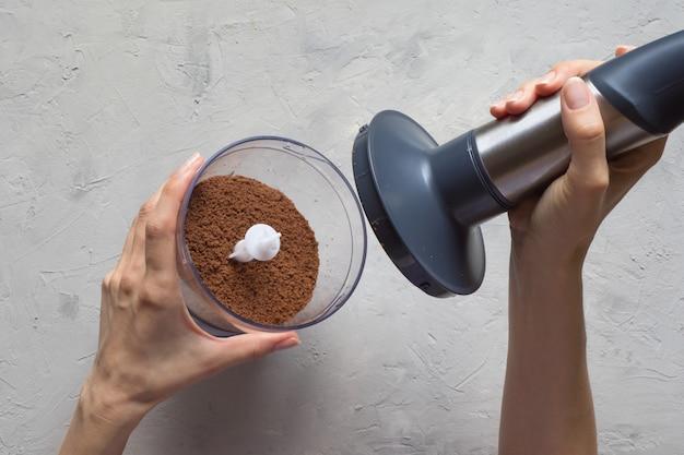 Blender na stole w kuchni. proces mielenia ziaren kakaowca w blenderze.