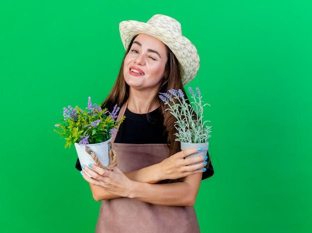 Blinked uśmiechnięta piękna dziewczyna ogrodnik w mundurze na sobie kapelusz ogrodniczy trzymając i krzyżując kwiaty w doniczce na białym tle na zielono