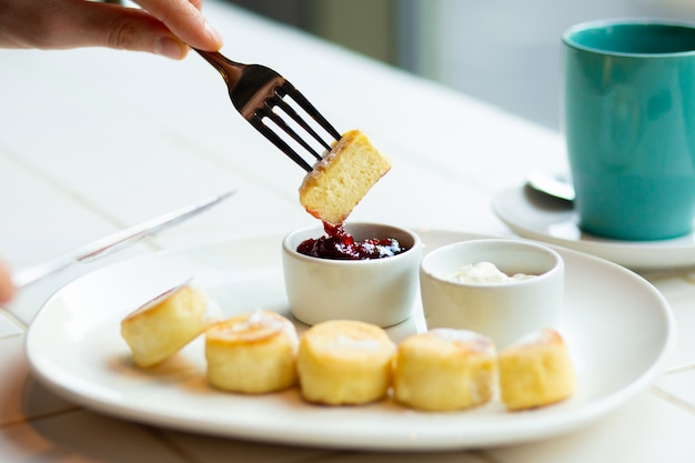 Bliny twarogowe z dżemem malinowym na białym talerzu, z bliska widok. zdrowe, smaczne śniadanie serniki z dżemem.