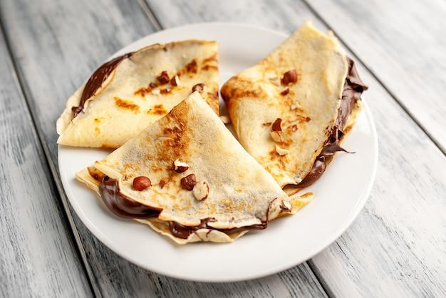 Bliny z czekoladowym rozszerzaniem się i hazelnuts, na białym talerzu na drewnianym tle