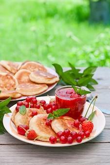 Bliny z jagodami na drewnianym stole w ogrodzie letnim