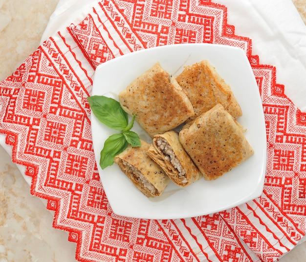 Bliny z mięsem na białym talerzu