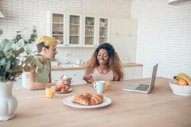 Bliscy ludzie. młody dorosły kaukaski kobieta pije kawę mówi i ciemnoskóry uśmiechnięty słuchanie o śniadanie w kuchni