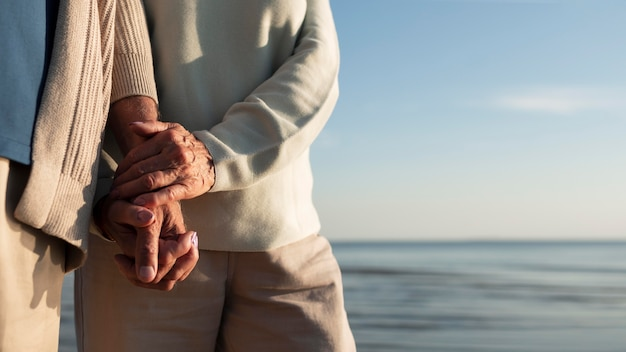 Bliscy partnerzy trzymający się za ręce nad morzem
