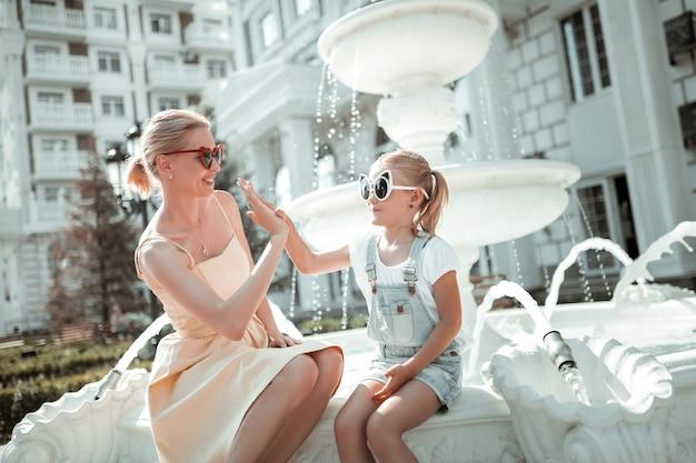 Bliscy przyjaciele. mała dziewczynka w dużych okularach przeciwsłonecznych siedzi z uśmiechniętą mamą nad piękną fontanną i przybija jej piątkę.