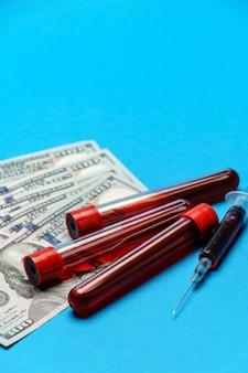 Bliska 100 rachunków dolarowych i próbki krwi w probówce na niebieskim tle