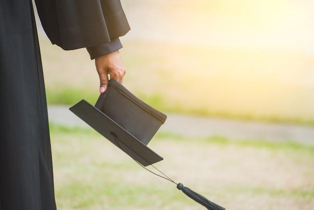 Bliska absolwent trzyma kapelusz. kształcenie w zakresie sukcesów na uniwersytecie