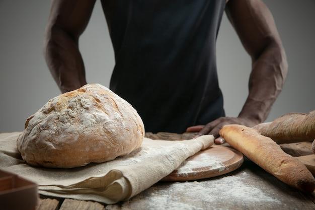 Bliska afro-człowiek gotuje świeże zboża, chleb, otręby na drewnianym stole. smaczne jedzenie, odżywianie, wyrób rzemieślniczy. żywność bezglutenowa, zdrowy tryb życia, ekologiczna i bezpieczna produkcja. wykonany ręcznie.