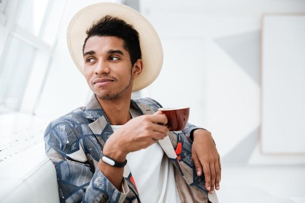 Bliska afrykański człowiek biznesu w niezwykłym garniturze i kapeluszu siedzi w biurze z kawą