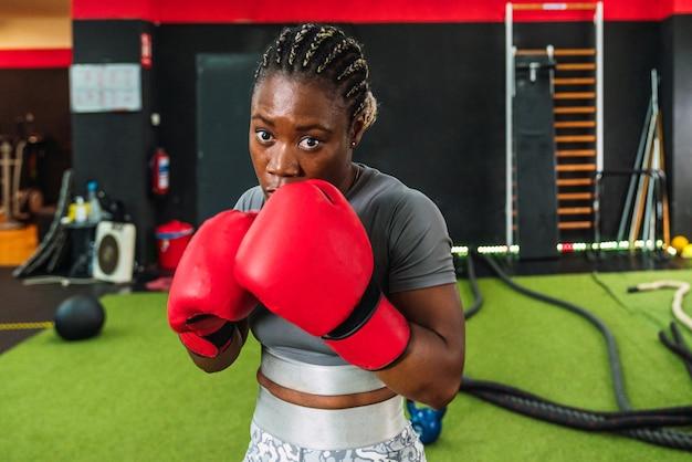 Bliska afryki lekkoatletka uprawiania boksu w siłowni. kobieta w stroju sportowym na siłowni robi trening bokserski w czerwonych rękawicach bokserskich