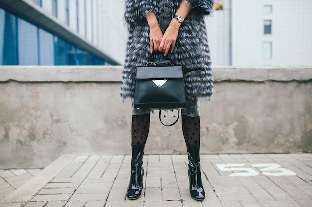 Bliska akcesoria szczegóły stylowej kobiety spacerującej po mieście w ciepłym futrze, sezon zimowy, zimna pogoda, trzymająca skórzaną torebkę, nogi w butach, obuwie trend w modzie ulicznej