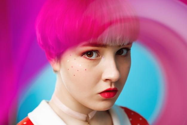 Bliska artystyczny pojęciowy portret pięknej lalki z krótkimi jasnofioletowymi włosami na sobie czerwoną sukienkę na niebieskiej ścianie rozmazany przód.