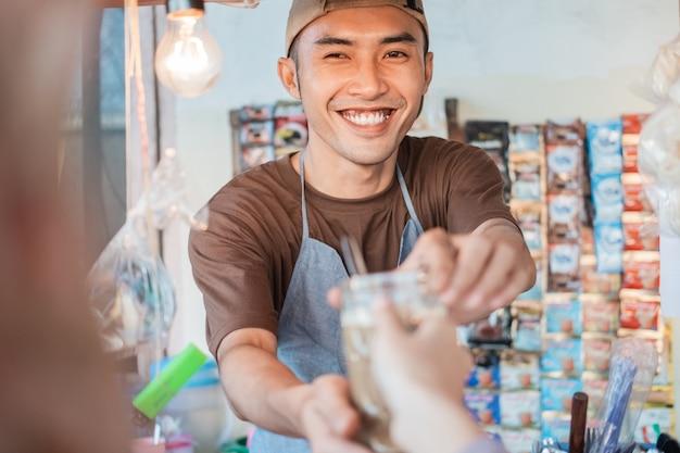 Bliska asian człowiek sprzedawca stoisko z wózkiem w fartuchu daje napoje klientom na straganie z wózkiem