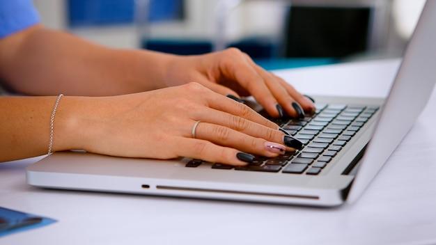 Bliska asystenta medycznego wpisując raport o stanie zdrowia pacjenta na klawiaturze laptopa, umawiając się na wizytę w klinice medycznej, rejestracja pacjenta. lekarz opieki zdrowotnej w medycynie jednolite pisanie zabiegów.