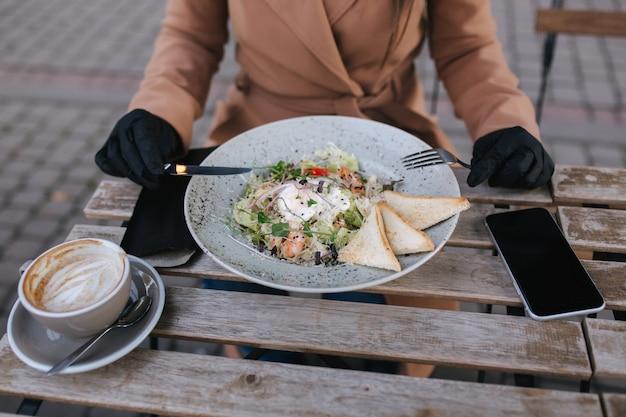 Bliska atrakcyjna młoda kobieta w czarnych rękawiczkach trzymać sztućce. koncepcja kawiarni podczas korantyny.