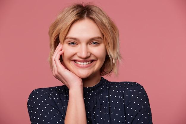 Bliska atrakcyjna radosna młoda piękna blondynka z krótką fryzurą ubrana w bluzkę w kropki, kokietki, flirtuje, uśmiecha się przyjemnie, na białym tle