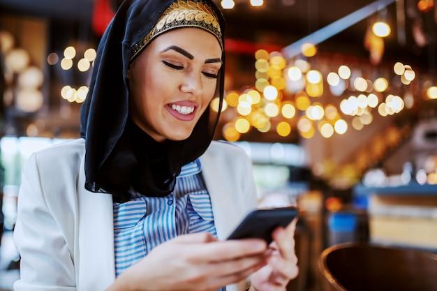 Bliska atrakcyjne pozytywne uśmiechnięte modnej muzułmańskiej kobiety siedzącej w kawiarni i za pomocą smartfona