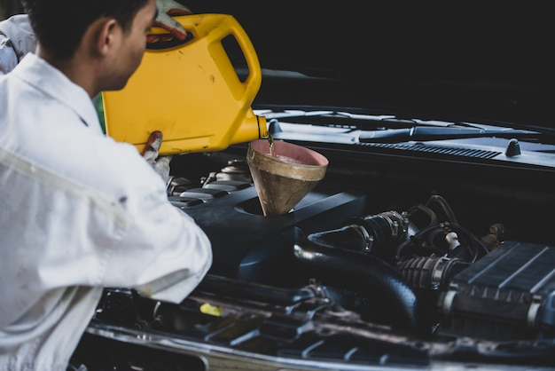 Bliska auto mechanik ręcznie wlewając i zastępując świeży olej do silnika samochodowego w warsztacie samochodowym. utrzymanie samochodu i koncepcja przemysłu