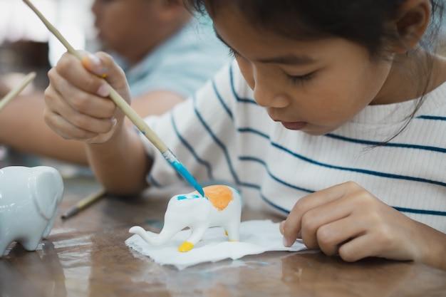 Bliska azjatycka dziewczynka koncentruje się na malowaniu na małym ceramicznym słoniu kolorem olejnym. zajęcia z twórczości plastycznej dla dzieci w szkole.