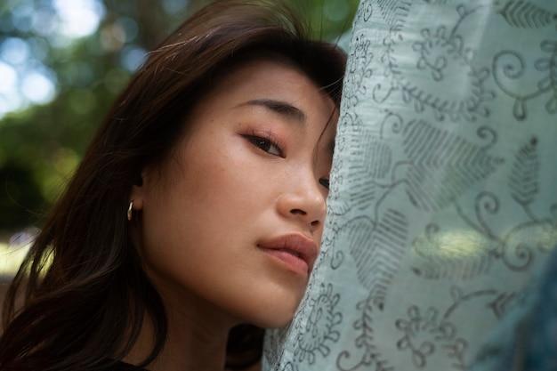 Bliska azjatycka kobieta pozuje z tkaniny