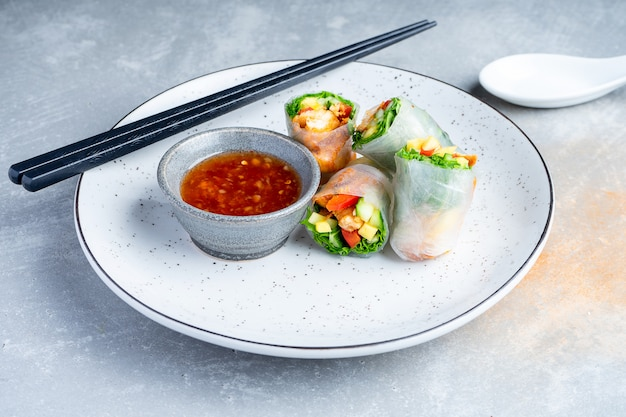Bliska azjatycka sajgonka z kurczakiem i czerwonym sosem
