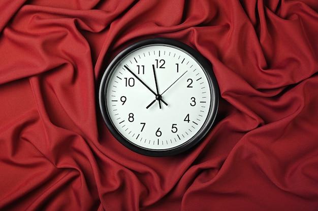 Bliska biała ściana klasyczny zegar na czerwonym tekstylnym tle ze złożonymi zakładkami tkaniny, podwyższony widok z góry, bezpośrednio nad